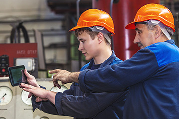 Two manufacturing workers view tablet